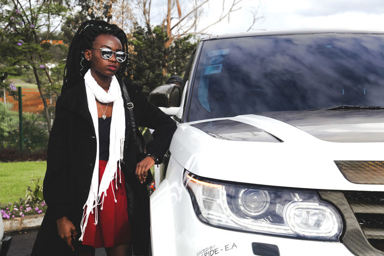 young lady standing next to luxury vehicle Motor Vehicle Mode Of Transportation Car Real People Glasses Land Vehicle Transportation Young Adult One Person Three Quarter Length Young Women Lifestyles Standing Sunglasses Fashion Front View Casual Clothing Day Leisure Activity Outdoors Teenager Hairstyle