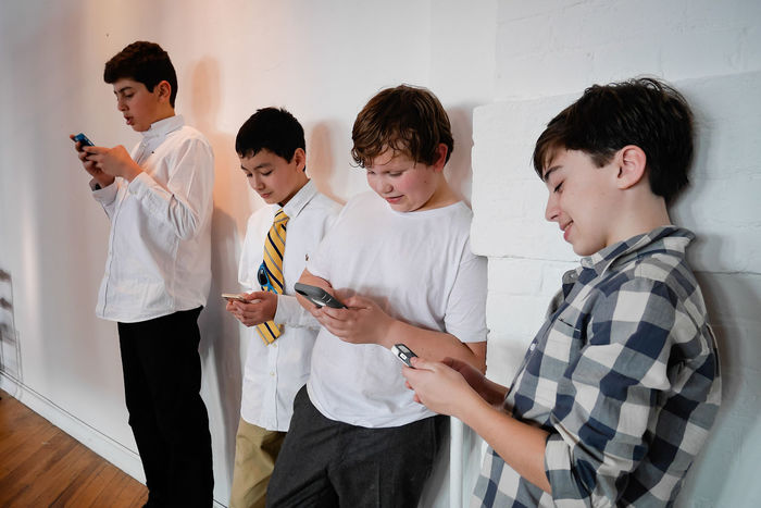 Boys with their cell phones Boys Communication Disassociated Happiness Holding Mobile Conversations Mobile Phone Mobile Phone Smart Phone Smiling Standing Student Technology Teenage Boys Teenagers  Teens Texting Texting Buddies Togetherness Wireless Technology