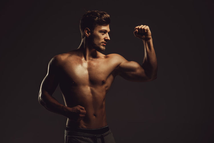 Athletic handsome man showing biceps muscles, studio shot Athlete Athletic Masculinity Abs Attractive Beauty Biceps Fitness Fitness Model Muscle Muscular Muscular Build One Person Physique  Showing Sport Sportive Sporty Standing Strong Studio Shot Torso Triceps Young Adult Young Men