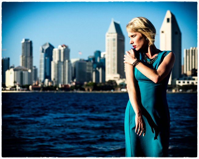 Portrait of young woman standing against sea and cityscape