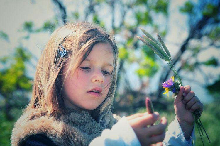 Girl holding flower at park