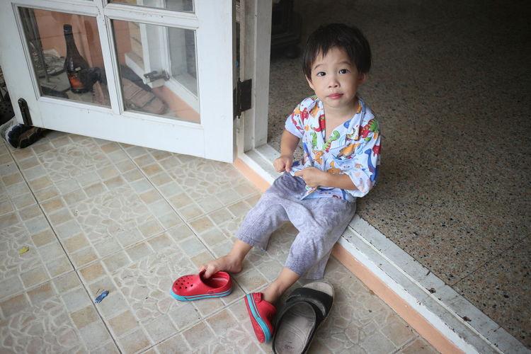 Portrait Of Young Boy Sitting In Doorway