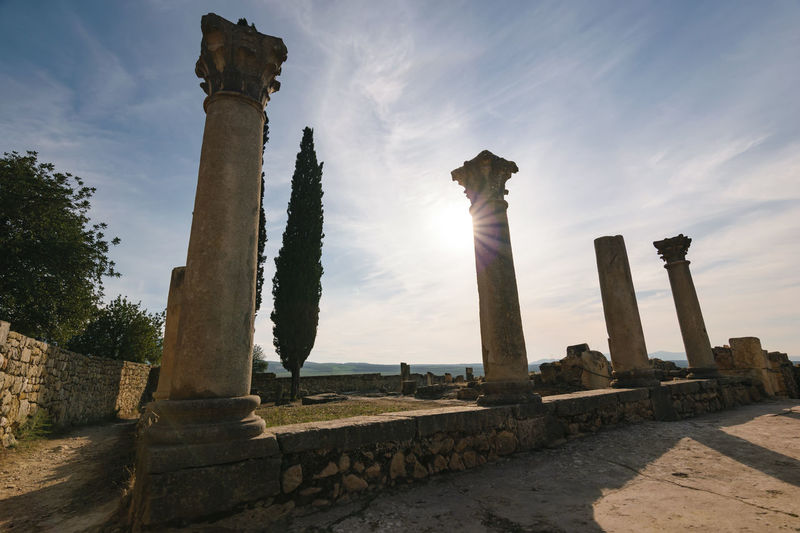 Some pillars of the roman ruins of Volubilis on a beautiful day with sunshine, blue sky and only few clouds photgraphed in horizontal format. Abandoned Africa Ancient Architecture Basilica Civilization Classical Column History Low Angle View Morocco No People Old Past Pillar Roman Ruin Sky Stone Temple Tourism Town Travel UNESCO World Heritage Site Volubilis