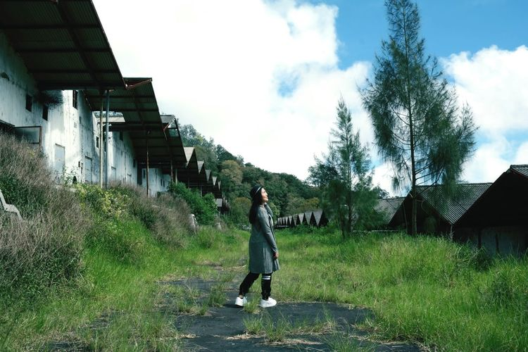 Full length of woman standing on field by houses against sky