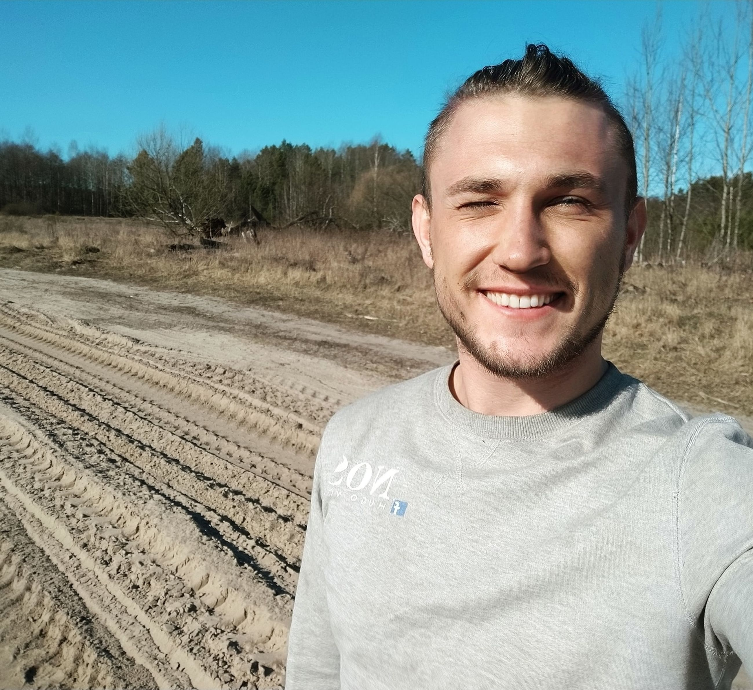 one person, smiling, portrait, adult, happiness, sky, nature, men, emotion, landscape, land, front view, young adult, rural scene, person, casual clothing, day, looking at camera, blue, clear sky, smile, environment, waist up, teeth, headshot, cheerful, outdoors, sunlight, standing, plant, field, sunny, soil, beard, dirt, lifestyles, leisure activity, tree