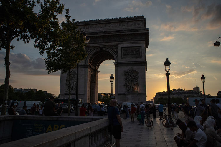Arc De Triomphe Arch Architectural Column Architecture Built Structure City Cloud - Sky Crowd Group Of People History Large Group Of People Lifestyles Nature Outdoors Real People Sky Sunset The Past Tourism Travel Travel Destinations Triumphal Arch