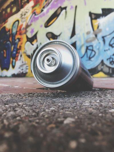 Aerosol Can On Road Against Graffiti Wall