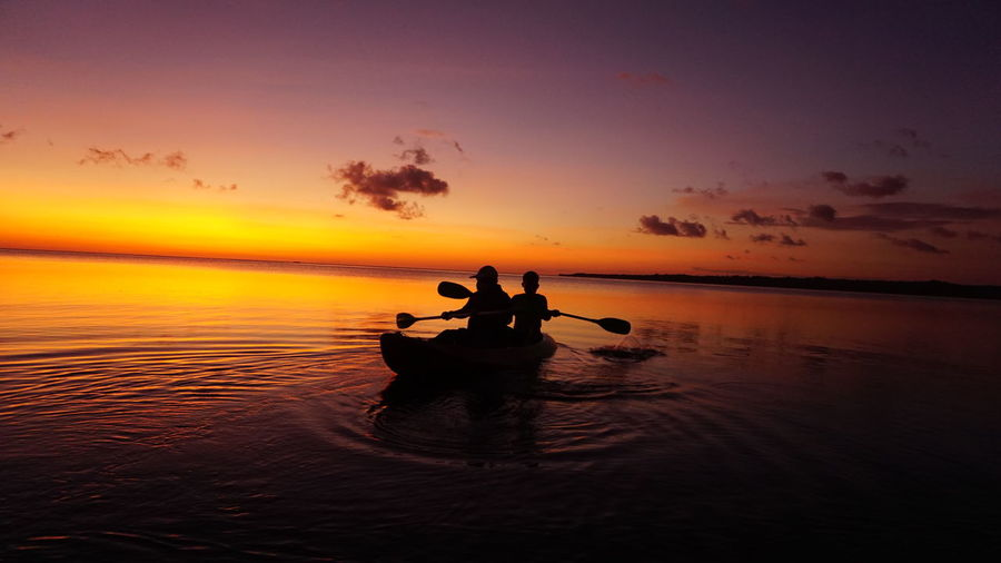 Silhouette people rowing boat in sea against sky during sunset