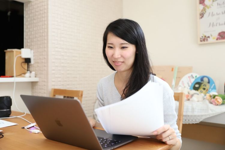 Smiley Face Smiling Working Woman Working Japanese Women Document Woman With Document One Person Laptop Technology Working Wireless Technology Smiling Indoors  Real People Business Using Laptop Women Happiness Sitting Young Women Table
