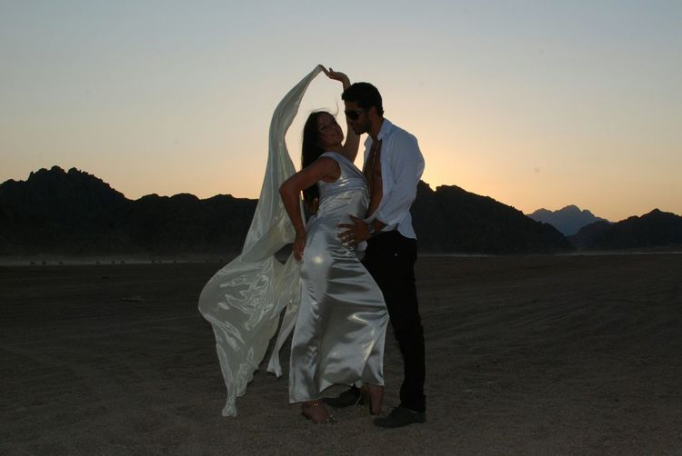 Full length of young man and woman standing at desert against sky