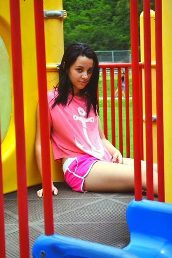 Portrait of young woman sitting by slide