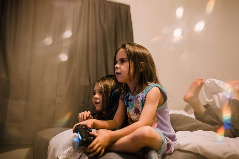 Siblings playing video games. Indoors  Sitting Real People Curtain Girls Bedroom Childhood Lifestyles Child People Day Young Adult One Person Adult This Is Family