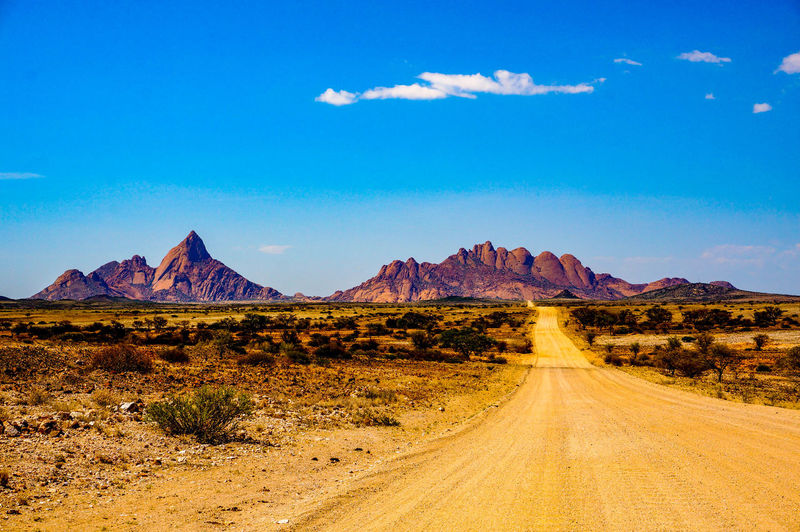 Dirt road leading towards rocky mountains against sky