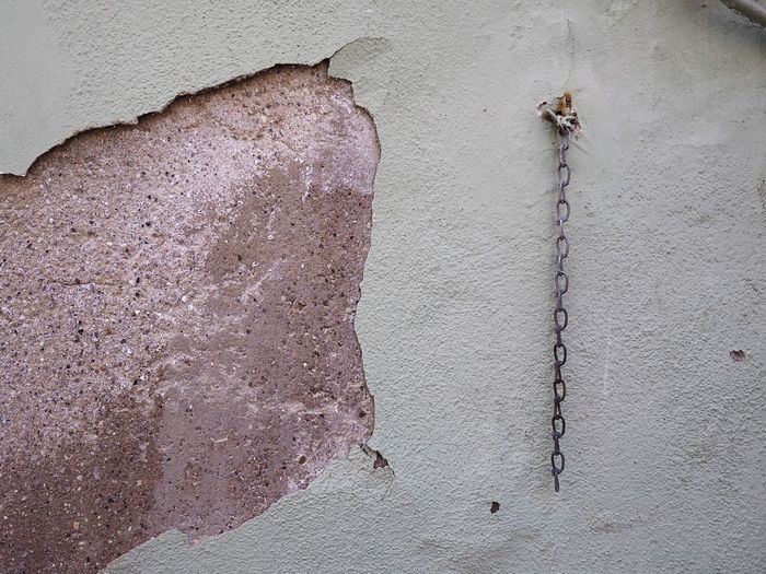 Chain Hanging On Damaged Wall