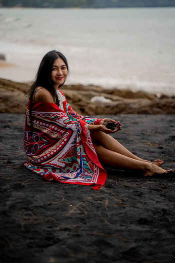 Portrait of woman sitting on land at beach