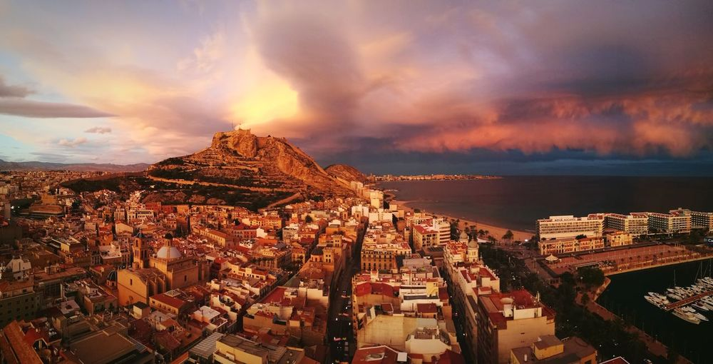 Aerial view of sunset over the castle and city against dramatic sky