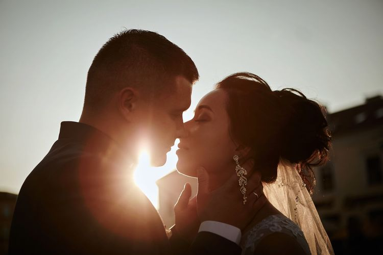 Close-Up Of Bride And Bridegroom Kissing Against Clear Sky