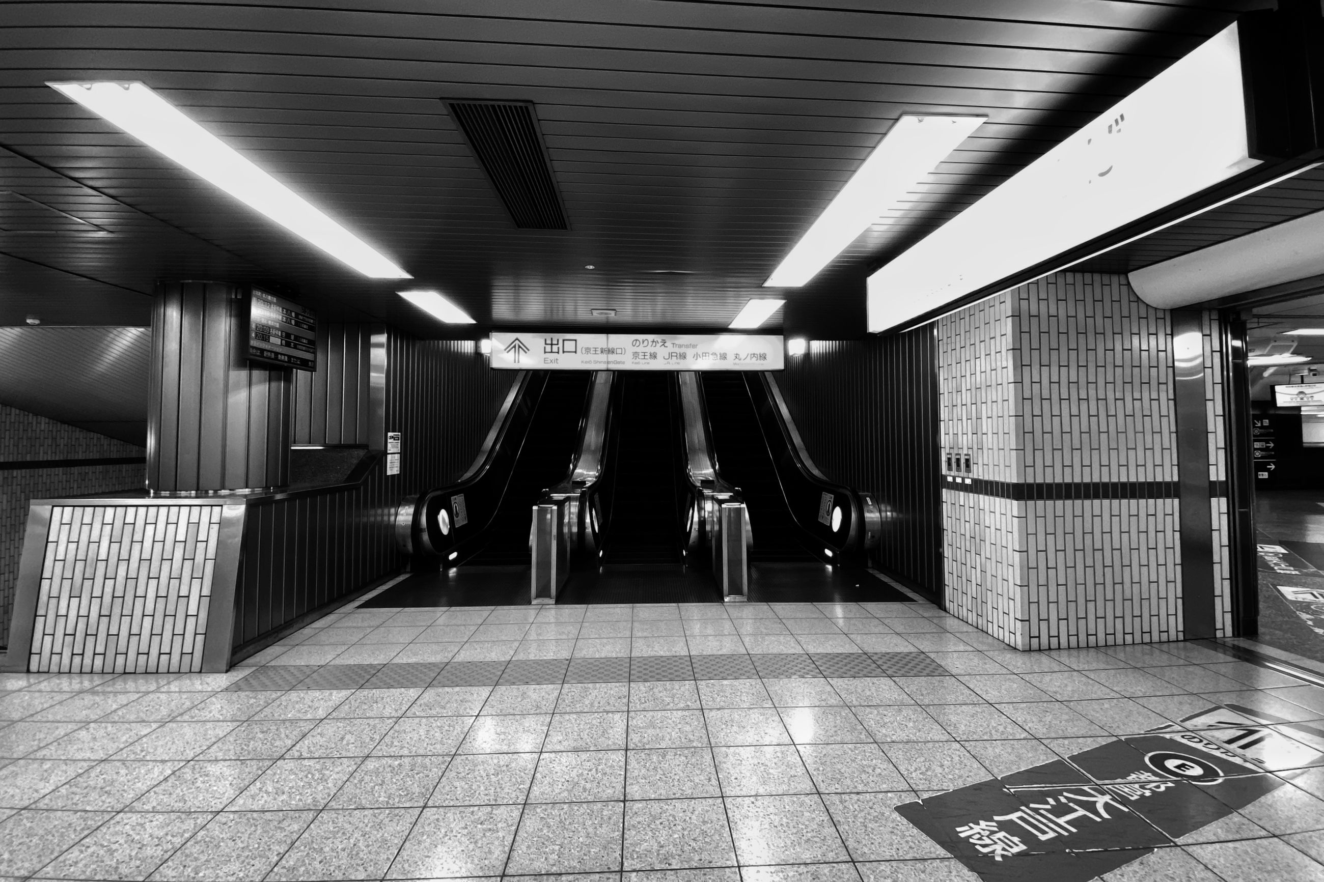 illuminated, architecture, sign, indoors, built structure, communication, public transportation, flooring, ceiling, transportation, direction, subway, architectural column, the way forward, text, tile, no people, tiled floor, subway station, information, modern, light, station