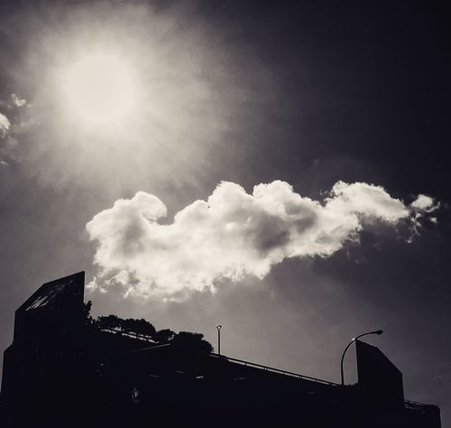 Cloud and sun in the sky Black And White Sky Cloud - Sky Building Exterior Low Angle View Architecture Built Structure Silhouette Building No People Outdoors Sunlight Day Sunbeam Sun