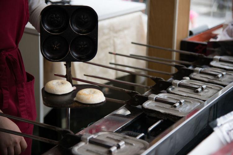 Cropped image of person preparing takoyaki