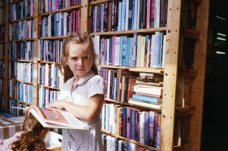 Portrait of girl with book standing in library
