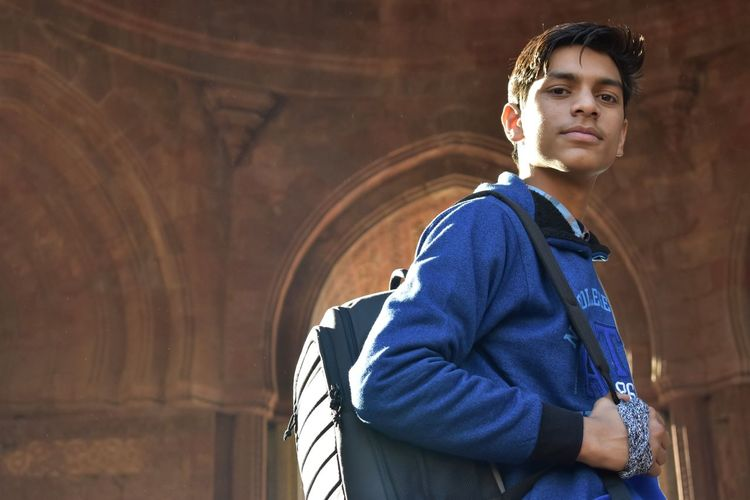 Portrait Of Young Man Looking Away While Standing In Historic Building