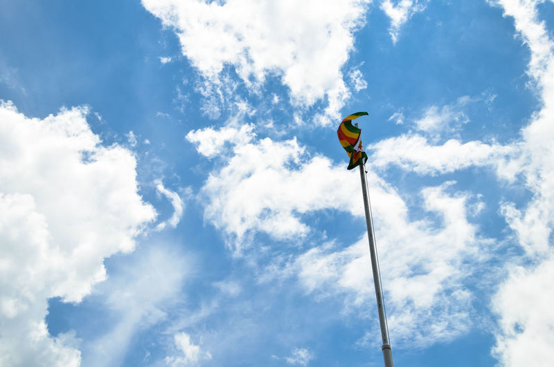 Low angle view of yellow flag against cloudy sky