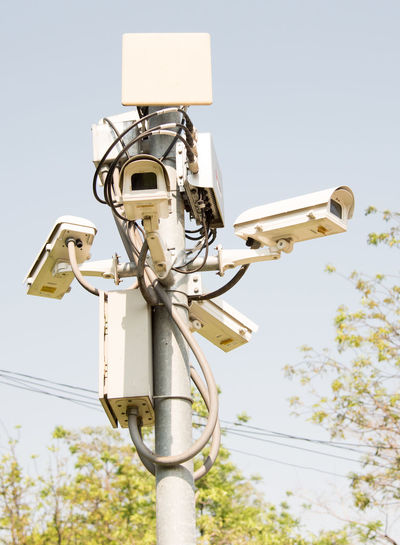 Low angle view of  surveillance camera against clear sky