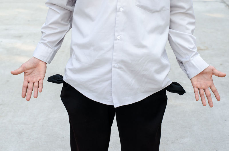 Midsection of man showing empty pockets on road