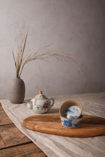 Tea cup on table against wall
