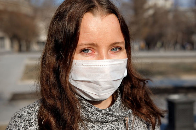 Close-up portrait of woman wearing mask outdoors during winter