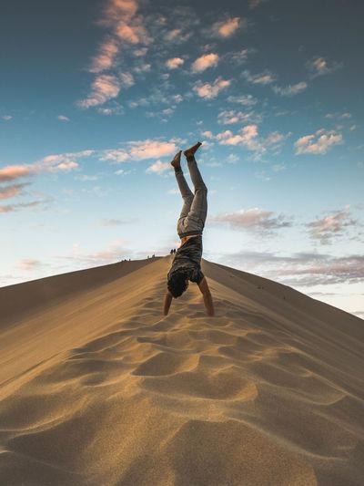 Man doing handstand in sand at dessert against sky