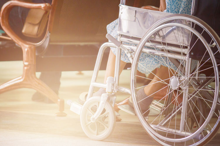 Low Section Of Woman Sitting On Wheelchair In Hospital