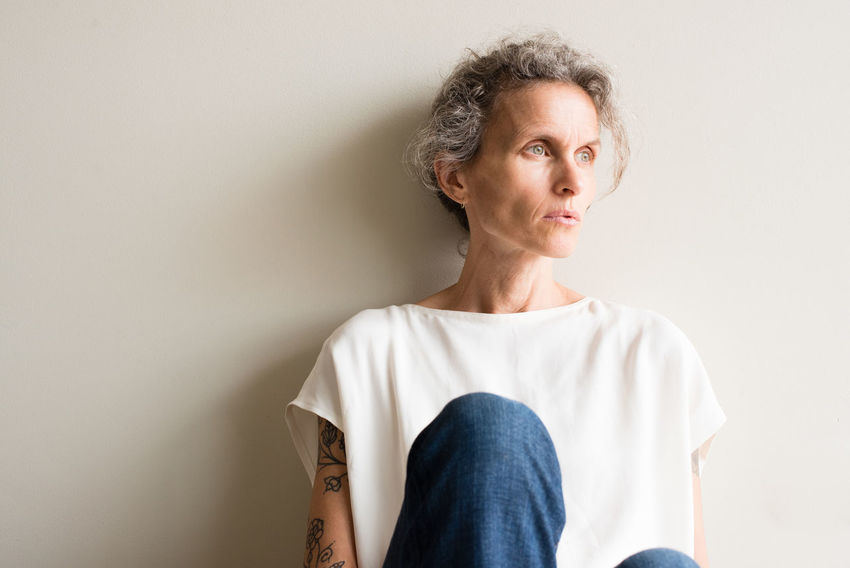 Middle aged woman looking pensive Adult Casual Clothing Contemplation Copy Space Depression - Sadness Front View Hairstyle Indoors  Jeans Lifestyles Looking Looking Away Mature Adult Mature Women One Person Portrait Short Hair Standing Studio Shot Wall - Building Feature Women