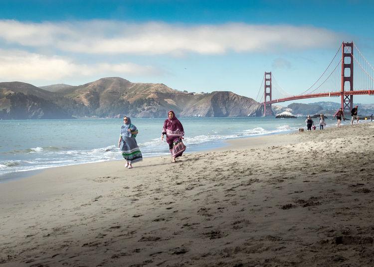 People on beach by suspension bridge over sea against sky