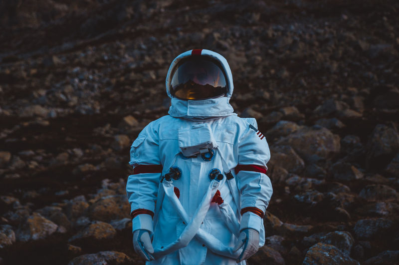 Astronaut looking away while standing in forest