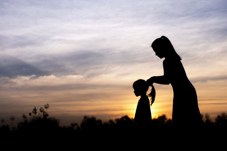 Silhouette of mother and daughter against sky during sunset