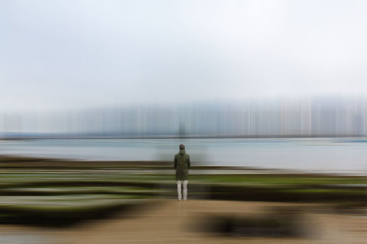 Rear view of man standing on water against sky