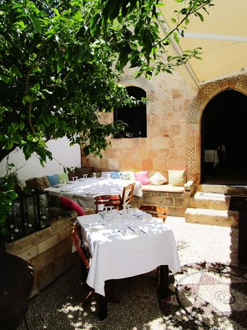 A greek restaurant Mediterranean  Restaurant Interior Decorating Food Chair Archway Entry Passage Historic Building Exterior Building Tablecloth