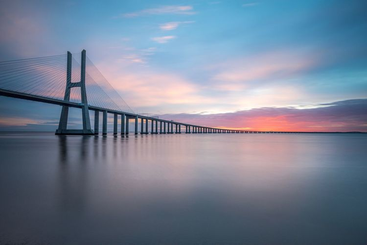 Vasco da gama bridge over tagus river against sky during sunset