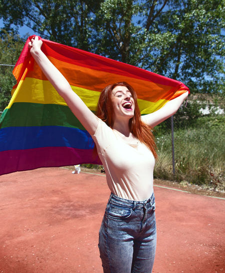 Cheerful Young Woman Holding Rainbow Flag On Basketball Court Against Trees