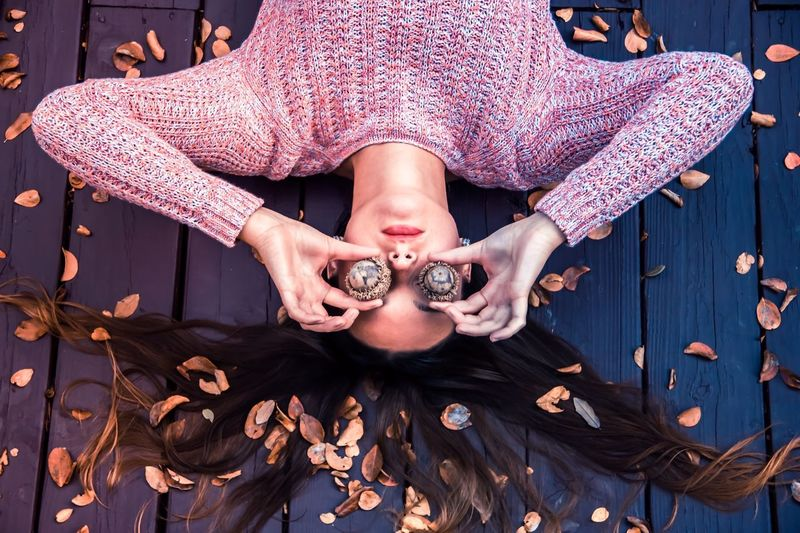 High angle view of woman with eyes covered by acorns on boardwalk