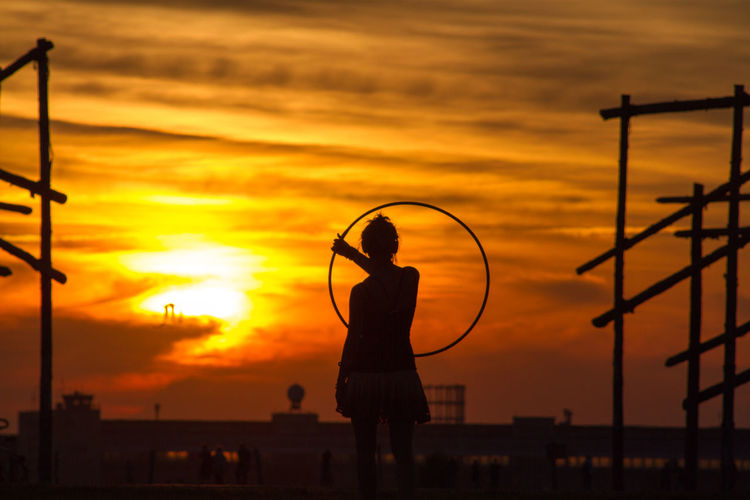 Silhouette of woman holding hula hoop at sunset