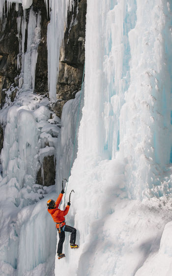 Low angle view of woman climbing on snowcapped mountain during winter