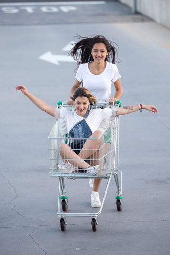 Excited girlfriends having fun and riding in shopping cart enjoying time together.