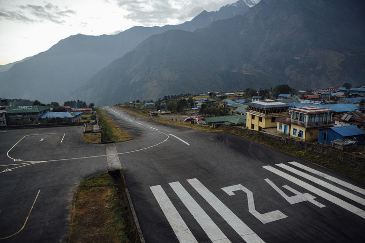Road amidst buildings and mountains against sky
