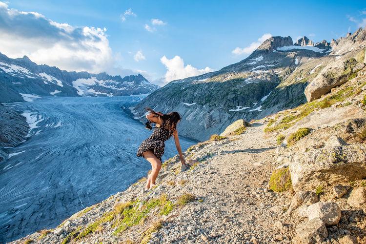 Full length of woman climbing on mountain
