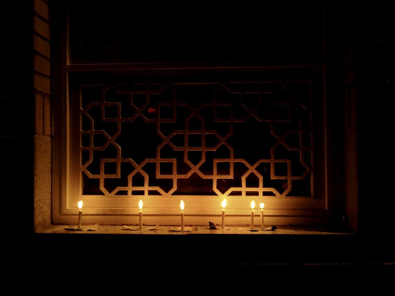 Lit candles on window in mosque at night