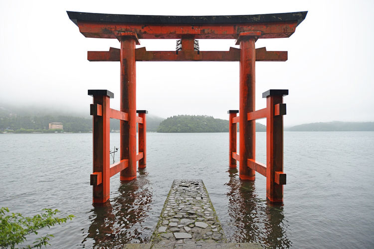Torii gate on the water at Hakone, Japan Architecture Beauty In Nature Cultures Day Japan Lake Nature No People Outdoors Peavey Reflection Sky Sunset Torii Gate Tranquility Travel Travel Destinations Water