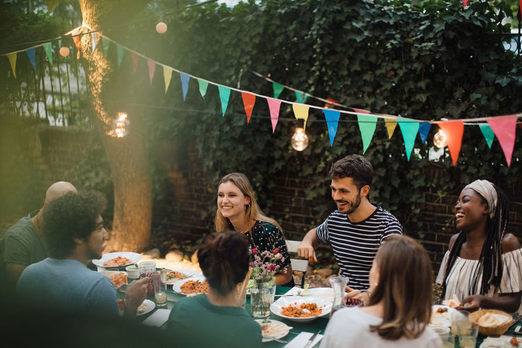 Multi-ethnic young friends enjoying dinner at table during garden party
